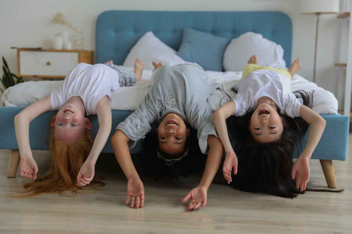 happy multiethnic little girls lying on bed