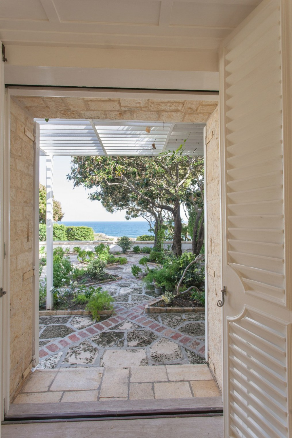 a white open door leads out to a garden and the ocean beyond