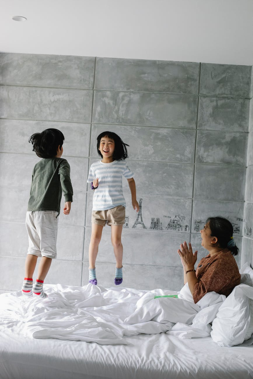 excited little ethnic children jumping on bed near clapping grandmother