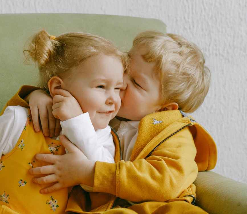 cheerful little siblings hugging in armchair at home
