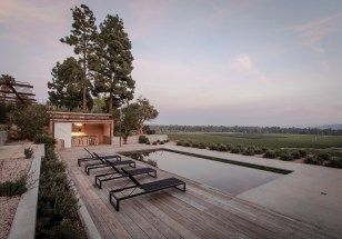 Twilight view, looking East, of the simply designed black bottom pool and pool house. The deck mixes sections of reclaimed wood and acid etched concrete. The poolside cabana with wet bar features corrugated steel and high fire rated cedar wood siding, sliding barn doors, and clerestory windows