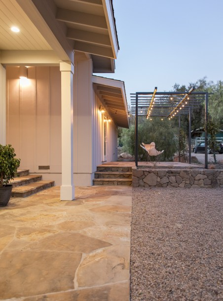 Flagstone pavers and steps lead either to the house's main entrance or to a raised patio off the master bedroom