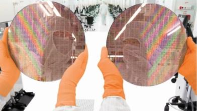 Obleas de chips AMD sostenidas por dos operarios con trajes de conejo