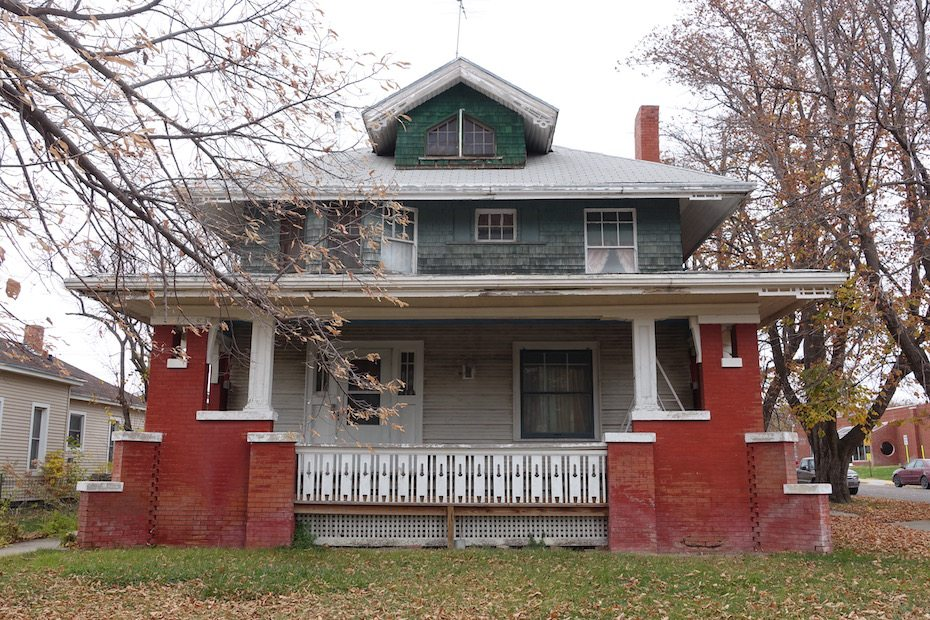 Facade. Note porch light centered on wall beneath porch roof.