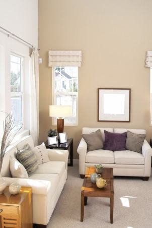 A Living Room In Light Taupe And Ivory With Side Tables In Varying Shades Of Wood From A Dark Finish To A More Natural Oak