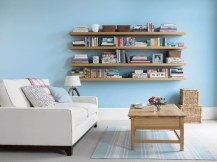 Home Living Room Storage Ideas Simple Blue Stained Wall Design With Wooden Rack Wall Ornaments Books Collection Elegant And White Sofa
