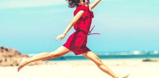 kobieta skacze ze szczęścia nad morzem