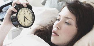 kobieta z budzikiem w łóżku