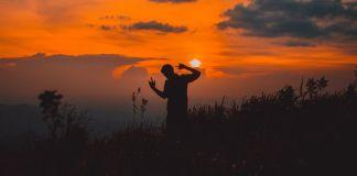 mężczyzna tańczący przy zachodzącym słońcu