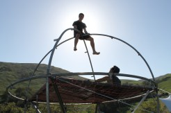 """An architecture student sits atop of the """"trampoline"""" structure. He reached it by jumping on the structure's trampoline-like floor to the top."""