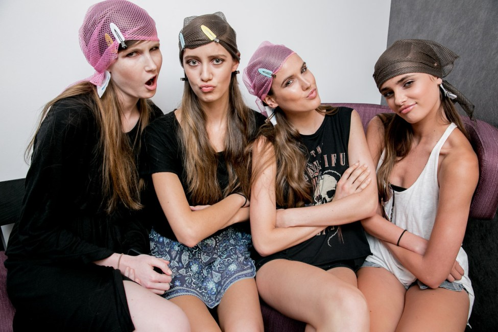 Models killing time backstage before their hair is finished