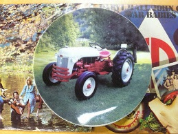 See if you can identify the album covers (or the musicians pictured) as background for the intriguing Ford Tractor plate.
