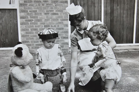 A nurse plays a fishing game with Thalidomide children