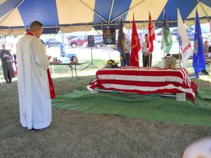 The Rev. Brian Jeffries, pastor of St. Joseph's Church in Canaan, says a prayer over the coffin as part of the Patriot Day Remembrance Saturday. The coffin is filled with all the names of those who died on September 11 and those who lost their lives fighting in Iran and Afghanistan. Ruth Epstein Republican-American