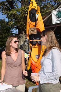 Laura Moore Brown, left, a member of the Warren Land Trust, talks with Bobbie Smith of Warren at the land trust's booth at the Warren Fall Festival on Saturday. The land trust is raffling off the kayak in the background. John McKenna Photo