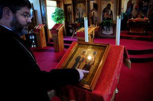 Father John Hopko, Pastor of Saints Cyril & Methodius Orthodox Church in Terryville, points out Cyrillic script on an icon of the church's patron saints in the church recently. Alec Johnson/ Republican-American