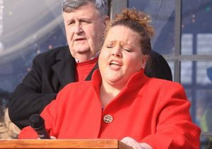 Lynn Whittaker of Torrington sings the national anthem at the opening of Torrington's Christmas Village on Sunday. Behind Whittaker is Mike Conway, master of ceremonies for the opening. John McKenna/RA
