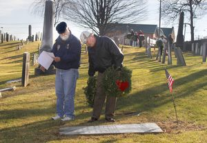 Mike Wilcox, US Navy Vietnam Veteran, and Bob Batters, from VFW Post 201 look to lay a wreath at the base of a headstone at the Old Burying Ground of Watertown Saturday afternoon during the Trumbell-Porter Chapter Daughters of the American Revolution Wreaths Across America ceremony to remember all United States Veterans. Jonathan Wilcox Republican American.