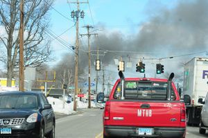 A plume of black smoke from a house fire at 64 Griswold St. wafts across East Main Street in Torrington on Monday. Alec Johnson/RA