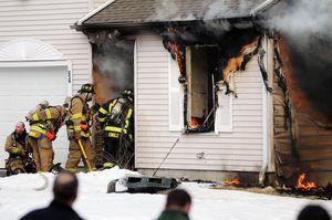 Firefighters enter a burning home at 64 Griswold St. in Torrington on Monday. Alec Johnson/RA