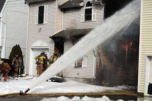Firefighters spray water on houses next to 64 Griswold St. in Torrington to keep a fire from spreading to them Monday. Alec Johnson/RA