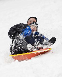 Dan Hall and his son Jeffery, 8, sled down the hill at Major Besse Park along Riverside Avenue in Torrington Friday. Erin Covey Republican-American.