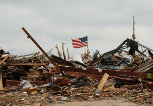 A flag continues to fly amidst the remains of tornado-destroyed homes in Moore, Okla., Monday. The Internet has made it easier for people all over the world to donate money after headline disasters like the the tornado and the school massacre in Newtown, Conn. (AP Photo/Sue Ogrocki)