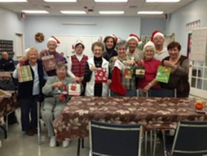 The Falls Avenue Senior Santas hold up the gift bags they hope to fill with donated holiday gifts and gift cards for local teens on Watertown's Holiday Family Assistance list. Through December 6, the Falls Avenue Senior Center is the drop-off location for gift cards and gifts for Watertown and Oakville teens in need. Cash and check donations also are accepted and will be used by the town's Social Services Department to purchase additional gifts. Catherine Dinsmore