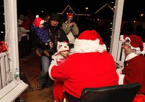 Ella Teixeira, 4, is all smiles as she meets Santa and Mrs. Claus with her parents Armando and Jackie Teixeira of Harwinton and sister Fiona age 16 months during the Annual Harwinton Hometown Holiday Celebration at the town hall Saturday evening. Jonathan Wilcox Republican-American.