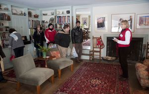 Joann King of Woodbury, a volunteer hostess, talks with guests about the music room in the home of John and Marija McCarthy.