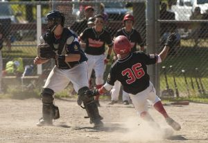 WATERBURY, CT--- -072215JS02--Waterbury's Armando Torres (36) slides past Greenwich's Kev Woodring (22) to score during their American Legion tournament game against Greenwich Wednesday at Bucks Hill Park in Waterbury.   Jim Shannon Republican-American