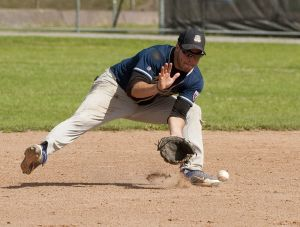 TORRINGTON, CT--- -080215JS22--Naugatuck's Mack Cianciolo (28) scoops up a ground ball during the Stan Musial championship game against Tri-Toan at Fuessenich Park in Torrington on Sunday. Naugatuck defeated Tri-Town 6-1.  Jim Shannon Republican-American