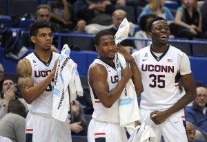 Connecticut's Shonn Miller, Rodney Purvis and Amida Brimah, left to right, react during the second half of their 83-43 victory over New Haven in an NCAA college basketball exhibition game in Hartford, Conn., on Saturday, Nov. 7, 2015. (AP Photo/Fred Beckham)