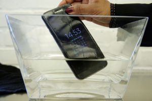 In this Feb. 22, 2016 file photo, a waterproof Samsung Galaxy S7 Edge mobile phone is submersed in water during a preview of Samsung's flagship store, Samsung 837, in New York's Meatpacking District. SquareTrade, a company that offers extended-protection plans for gadgets, said the Galaxy S7 and S7 Edge still functioned after being submerged in water for 30 minutes. Audio was ìpermanently muffled and distortedî after the dunking, but the Samsung phones still outlasted Appleís iPhones in SquareTradeís water tests. The study, released Monday, March 14, also found that Samsungís new phones are more prone to breaking than the iPhone 6S, which survived 30 seconds in a tumbling test chamber, similar to a dryer without heat. (AP Photo/Richard Drew, File)