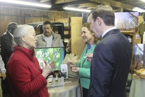 19_NEW_031816JN04 - Kay Carroll, a maple sugar farmer from Brookside Farm II in Litchfield, gives U.S. Senator Christopher S. Murphy and U.S. Representative Elizabeth H. Esty a sample of some of the Maple Syrup produced by the Woodbury Sugar Shed part of The Farm in Woodbury, Connecticut. John Nestor Republican-American