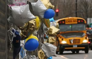 A school bus rolls towards a memorial for victims of the school shooting in Newtown Dec. 18, 2012. Classes resume Tuesday for Newtown schools except those at Sandy Hook. Buses ferrying students to schools were festooned with large green and white ribbons on the front grills, the colors of Sandy Hook. At Newtown High School, students in sweatshirts and jackets, many wearing headphones, betrayed mixed emotions. Adam Lanza walked into Sandy Hook Elementary School and opened fire, killing 26 people, including 20 children, before killing himself. (AP Photo/Charles Krupa)