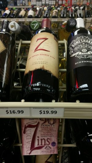A promotion for a bottle of Michael David Winery's 7 Deadly Zins touts a 90 point review by wine critic Robert Parker. The bottle on the shelf above it at Fine Wine and Liquor in Naugatuck is a 2012 vintage. The store's owner removed the promotion after a reporter pointed out the inconsistancy. Laraine Weschler Republican-American
