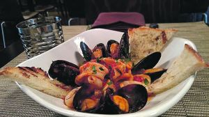 Mussels & Calamari, sautéed in a white wine tomato broth and served with garlic toast. Jack Coraggio