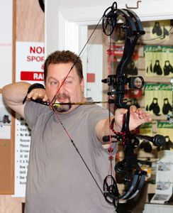 Scott Murray, archery sales, manager and certified trainer for Northwest Sporting Goods in Winsted lines up a shot inside the indoor archery range on Wednesday. Murray says there has been an increasing popularity of bowhunting. Darlene Douty Republican-American