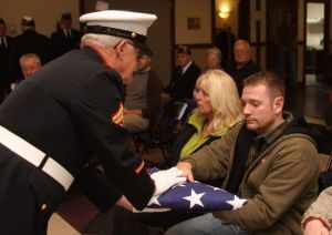 cutline attribution name:John McKenna republican-american Peter Donahue, grandson of American Legion Post 44 veteran of the month Frederick C. Maurer, presents his late grandfather's flag to Post 44 representative Brian Richardson during Saturday's service at the Bantam Borough Hall.