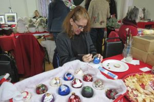 Tamara Polk decorates ornaments at Saturday's Holiday Fair at the United Church of Christ in Cornwall. An artist, she said when she was 19 she decided her Christmas tree was 'boring,' so she began creating her own decorations. Polk, whose Scandinavian grandmother taught her many recipes, had examples of holiday cookies on hand, including krumkate, rosettes, sanbakkels, fattigman and bakkels. Ruth Epstein Republican-American