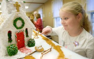 Allie Goulet, 7, of Watertown checks out the Country Church her grandma made during the annual Gingerbread Village and Christmas Bazaar at St. George's Episcopal Church in Middlebury Saturday. Steven Valenti Republican-American
