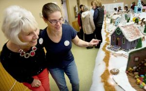 From left, Beverly Odonnell of Southington and Kristine Boisits of Middlebury check out Kristine´s Church of New Life gingerbread church during the annual Gingerbread Village and Christmas Bazaar at St. George's Episcopal Church in Middlebury Saturday. Steven Valenti Republican-American