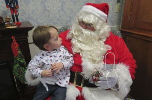 James Dawson lll, 2, of Southfield, Mass., tells Santa what he'd like for Christmas during Geer's Holiday Bazaar Saturday. Ruth Epstein Republican-American