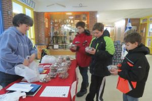 North Canaan Elementary School PTO President Nikki Blass sells containers of treats to, from left: brothers Diontae, Dason and Demetri Ouellette during last week's Chocolate Fest to raise money for the PTO Scholarship Fund. Ruth Epstein Republican-American