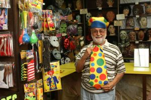 Michael Rinaldi, owner of Arabesque Dance and Costume on Bank Street in Waterbury, dons a clown hat and tie at his store Wednesday. Laraine Weschler Republican-American