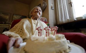 Emma Morano holds a cake with candles marking 117 years in the day of her birthday in Verbania, Italy, Tuesday, Nov. 29, 2016. At 117 years of age, Emma is now the oldest person in the world and is believed to be the last surviving person in the world who was born in the 1800s, coming into the world on Nov. 29, 1899. (AP Photo/Antonio Calanni)