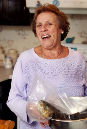 Maria Silva carries a trout to be cook while in her kitchen in Prospect Monday. Silva will appear in Food TV´s ÔClash of the Grandmas´ which airs December 4th. Steven Valenti Republican-American