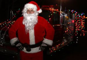 John Caron of the Bantam Fire Company, playing Santa during the Bantam Historical Society's tree lighting, stood in front of the fire company truck he decorated with lights.