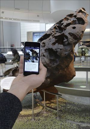 In this Dec. 12, 2016 photo provided by the American Museum of Natural History, a visitor uses the museum's flagship app Explorer which acts like a virtual curator, teaching visitors about the surprising facts and stories, near the Willamette Meteorite at the museum in New York. Museums working to present exciting and meaningful exhibits are increasingly relying on technology. (Roderick Mickens/American Museum of Natural History via AP)